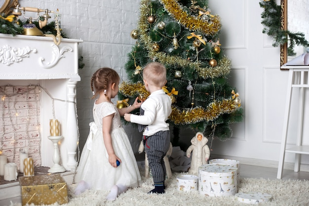 Children near the christmas tree, a boy and a girl dress up the christmas tree Premium Photo