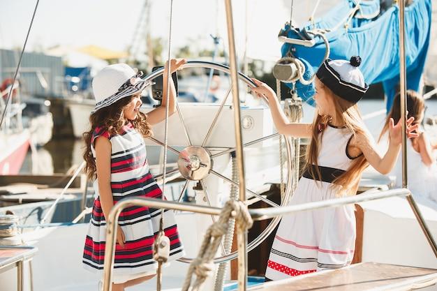 オレンジジュースを飲む海のヨットに乗っている子供たち。屋外の青い空に対して10代または子供の女の子。カラフルな服。キッズファッション、晴れた夏、川、休日のコンセプト。 無料写真