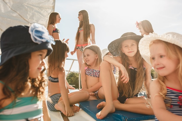海のヨットに乗っている子供たち。 10代または子供の女の子の屋外。 無料写真