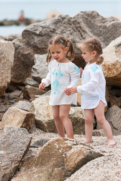 海のビーチで子供たち。双子が石と海の水に立ち向かいます。 無料写真