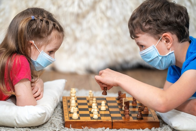 Premium Photo | Children play chess in medical masks on the face, lie on  the floor. stay at home