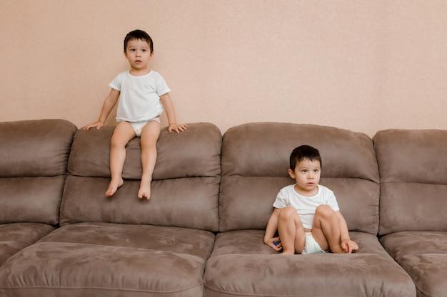 Дети играют в комнате дома. близнецы двух лет прыгают на диване Premium Фотографии