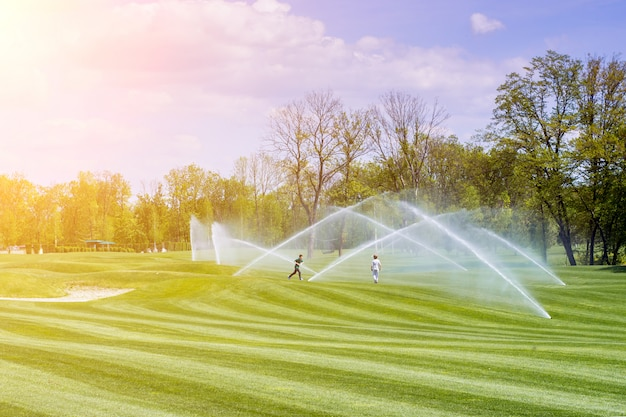 Children play under the streams of watering station golf courses Premium Photo