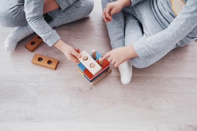 子供たちは子供部屋の床でおもちゃデザイナーと遊ぶ。カラフルなブロックで遊ぶ2人の子供。幼稚園教育ゲーム 無料写真