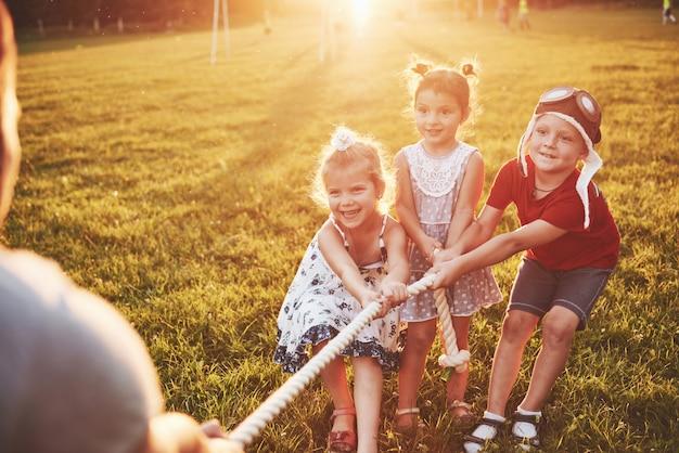 Дети играют с папой в парке. они тянут веревку и весело лежат в солнечный день Бесплатные Фотографии