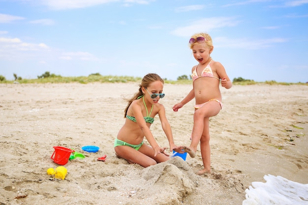 Children play with sand on beach. girl breaks castle of sand, girlfriend screams. Premium Photo