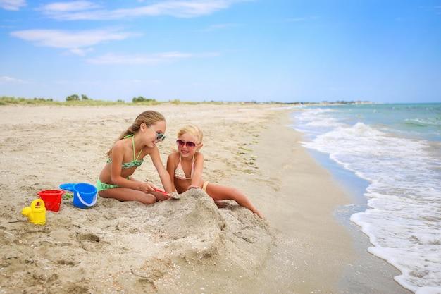 Children play with sand on beach. Premium Photo
