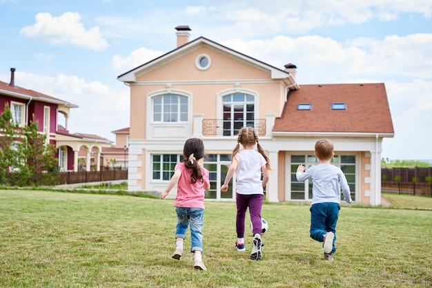 Дети играют у красивого дома Premium Фотографии