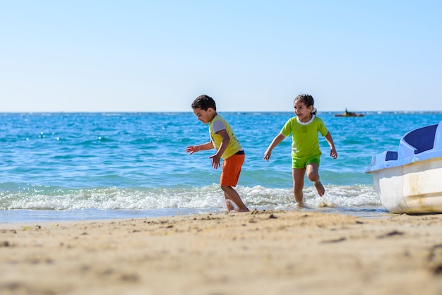 Children playing at sea shore under sunlight Premium Photo