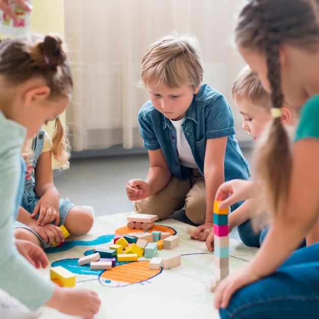幼稚園で一緒に遊んでいる子供たち 無料写真
