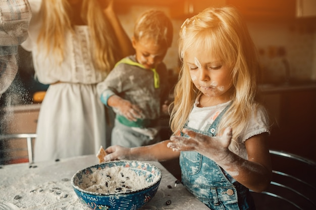 Children playing with a bowl of flour Free Photo