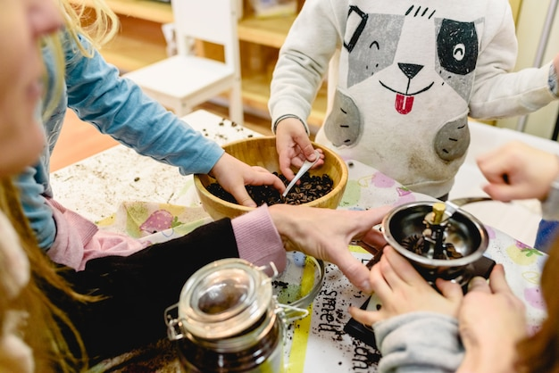 Children playing with a coffee grinder in a montessori class. Premium Photo