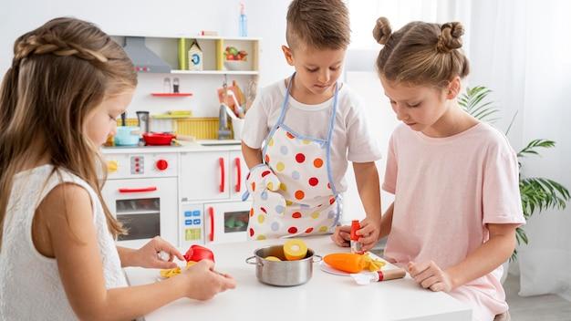 Bambini che giocano con un gioco di cucina Foto Gratuite