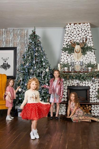 クリスマスツリーのインテリアの背景にポーズの子供たち Premium写真