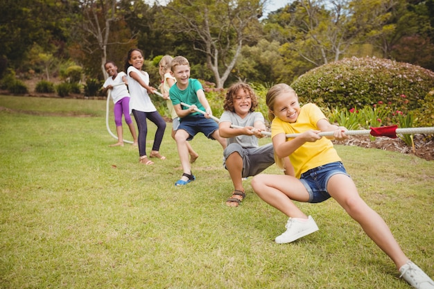 Children pulling a rope in tug of war Premium Photo