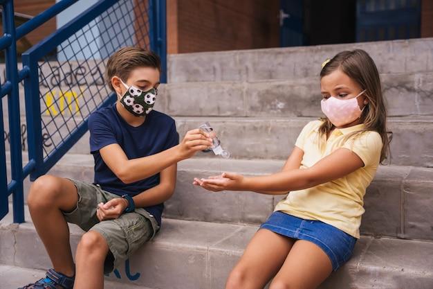 授業中に学校の教室で消毒ジェルを手につけている子供たち。 covidパンデミック中に学校に戻る Premium写真