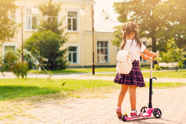 Children riding scooters on their way to school Premium Photo