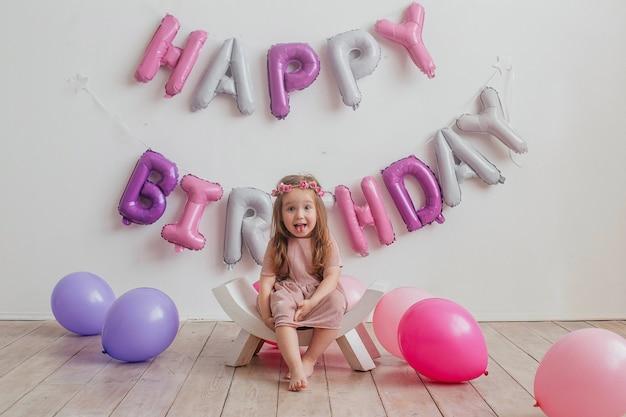 아이들의 생일. 행복 한 어린 소녀는 카메라 앞에서 포즈, 웃는 아이 혀를 보여줍니다. 프리미엄 사진