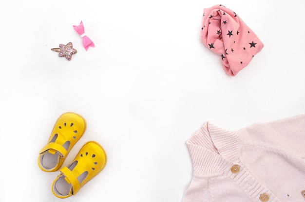 어린이 의류와 신발은 흰색 배경 상위 뷰에 배치됩니다. 텍스트를위한 공간입니다. 프리미엄 사진