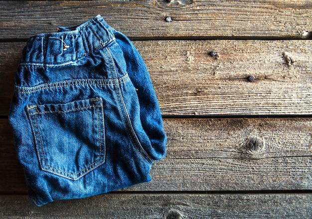 Детская одежда, джинсы на деревянной форме. одежда, стиль, мода Premium Фотографии