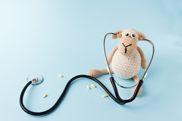 Children's doctor concept. sheep toy and stethoscope on blue background Premium Photo