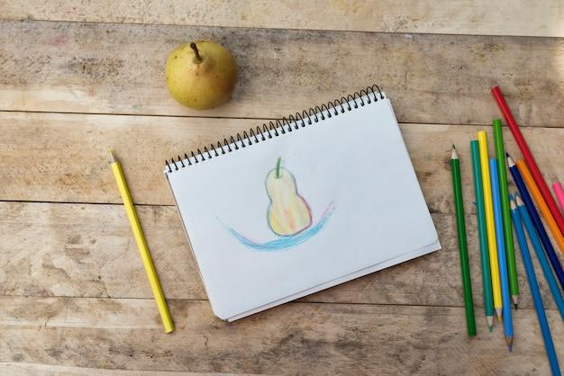 子供の絵、梨、色鉛筆。木製のテーブル。上面図 Premium写真