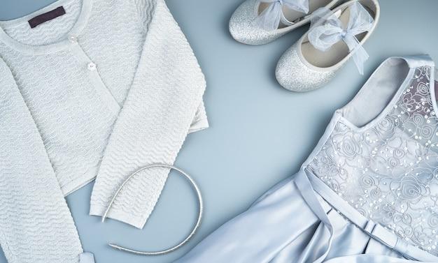 회색 파란색 배경에 어린이 드레스, 재킷, 신발 및 보석. 프리미엄 사진