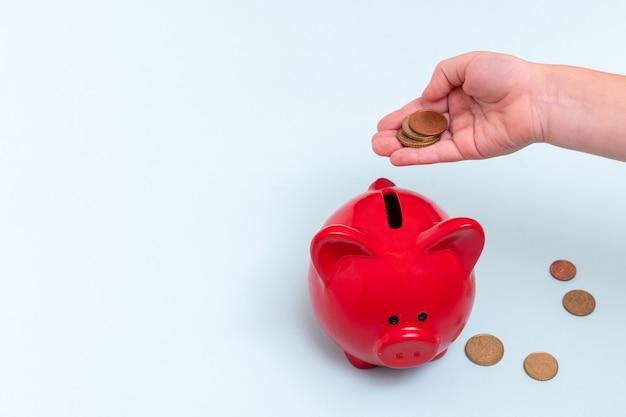 子供の手は、青い貯金箱の上にいくつかのコインを持っています。 Premium写真