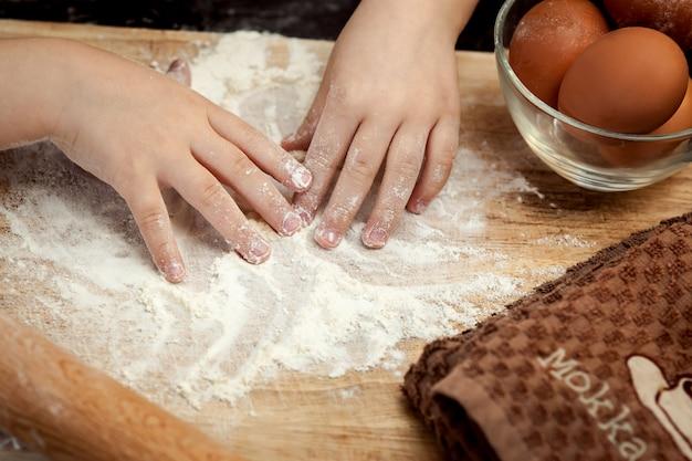 Children's hands in flour. cooking egg pie Premium Photo