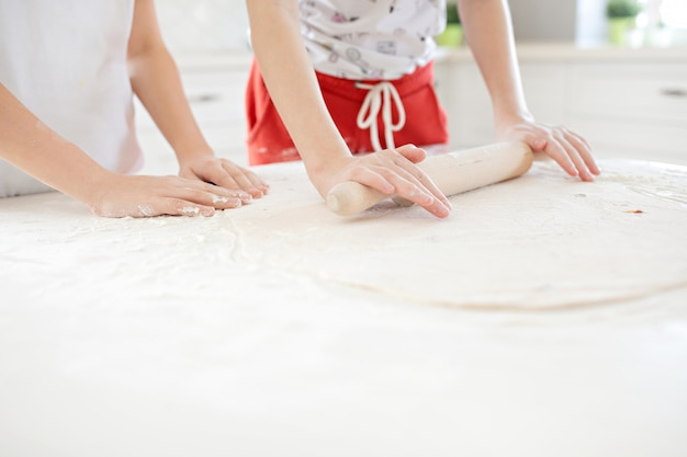 Children's hands roll out the pizza dough on a white table. having fun together in the kitchen. view from above. Premium Photo