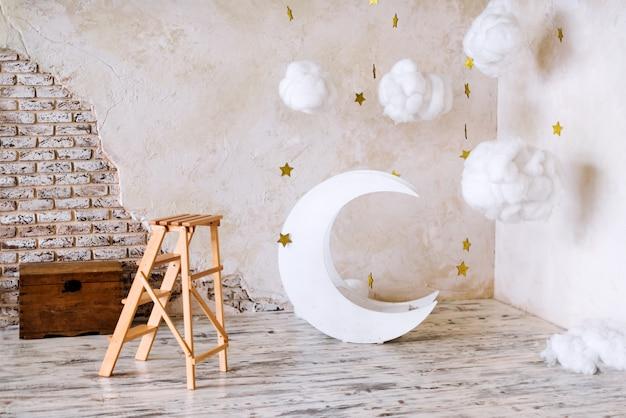 写真撮影のための子供の場所。月と星と雲の夢のような装飾。インテリアの要素。 Premium写真