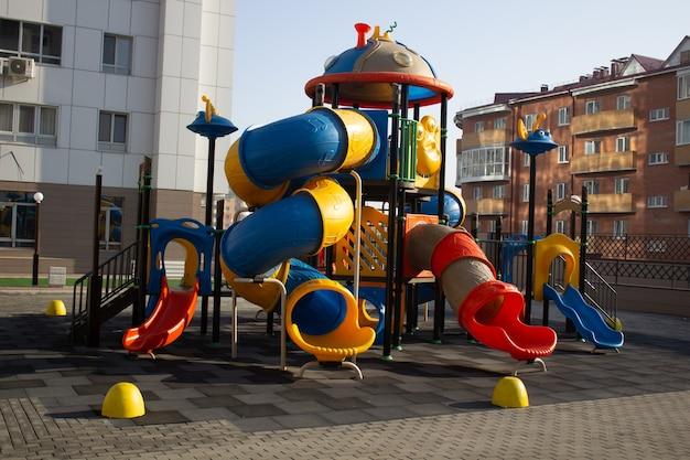 Детская разноцветная пластиковая площадка во дворе многоэтажного дома. Premium Фотографии