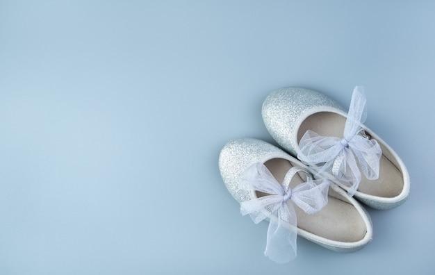 회색 파란색 배경에 어린이 실버 휴가 신발. 프리미엄 사진