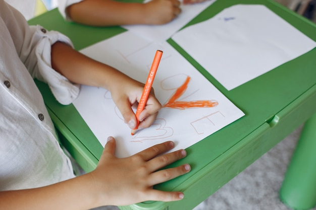 Children siting at the green table and drawing Free Photo