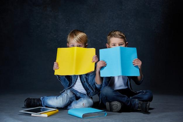 本を床に座っている子供たち 無料写真