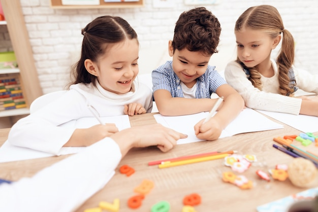 Children smile and write in notebooks with a pen. Premium Photo