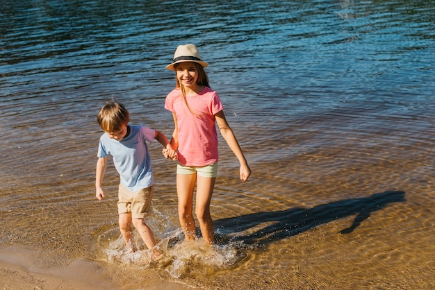 Children splashing in water at beach Free Photo