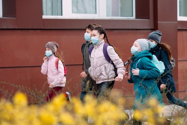 医療用マスクをつけた児童生徒が学校を去る。 Premium写真