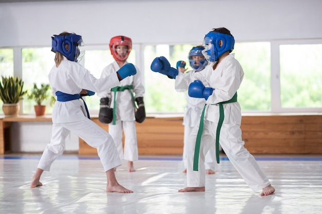 Children studying martial arts wearing helmets while boxing Premium Photo