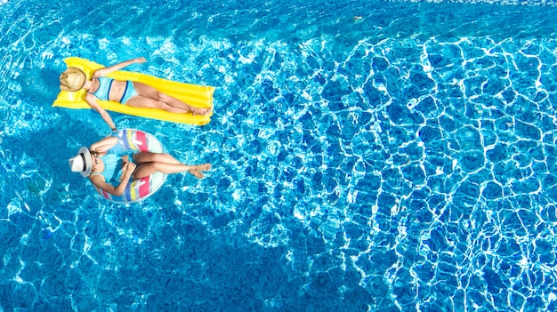 Children in swimming pool aerial drone view fom above, happy kids swim on inflatable ring donut and mattress, active girls have fun in water on family vacation on holiday resort Premium Photo