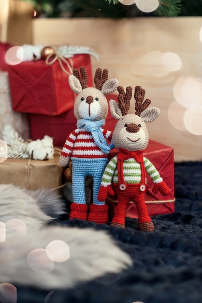 Children toys. two stylish amigurumi deers in striped sweaters, scarf and butterfly tie stands near christmas presents. Premium Photo