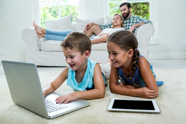 Children using laptop in front of parents at home Premium Photo