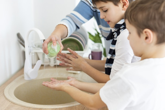 Children washing their hands with the help of their mother Free Photo