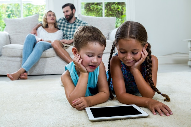 Children watching digital tablet screen while parents in background Premium Photo