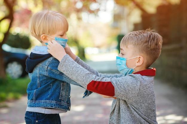 Дети носят медицинские маски на открытом воздухе. мальчик помогает надеть маску на лицо своему младшему брату. Premium Фотографии