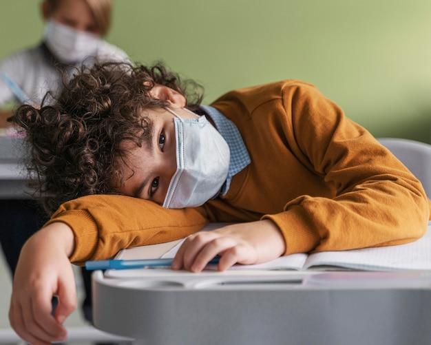 Дети в медицинских масках скучают на уроках в школе Бесплатные Фотографии