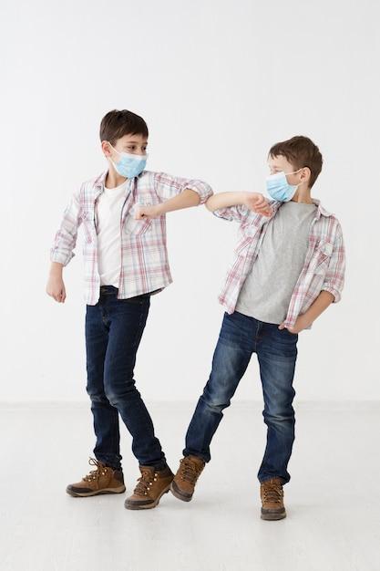 非接触式の挨拶を示す医療用マスクを持つ子供 無料写真