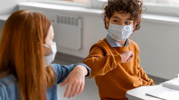 Дети с медицинскими масками салютуют локтями в классе Бесплатные Фотографии