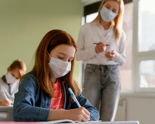 여성 교사와 학교에서 학습 의료 마스크를 가진 아이들 무료 사진