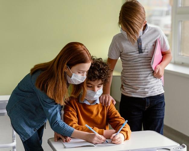 学校で学習している医療用マスクを持つ子供 無料写真